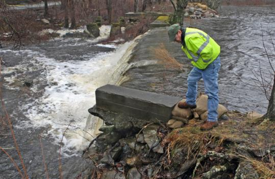 Engineer Edward Hughes checked the water levels at the Forge Pond Dam in Freetown in March as rising water posed a threat.