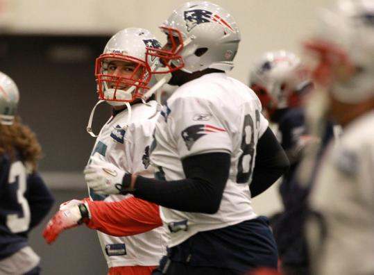 Aaron Hernandez (left) was with Alge Crumpler and his teammates at practice, but was limited by a hip injury.