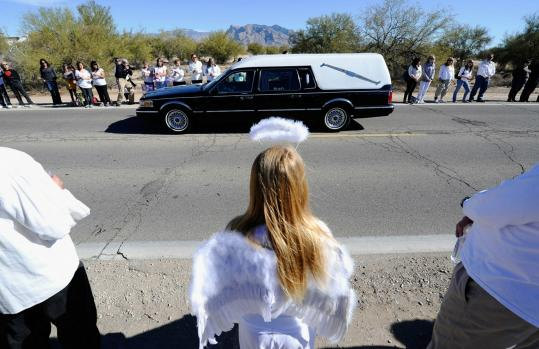 Lindsey Lummus, 10, wore an angel costume as a hearse carried Christina Taylor Green to the funeral in Tucson yesterday