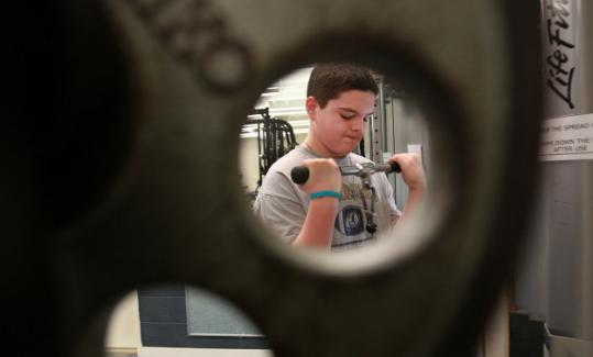 Zach Smith works out on one of the machines at the new wellness center at Foxborough High School.