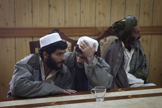 Khan Mohammed (left), who was linked to a rocket attack, sat with another detainee and a tribal elder before his release.