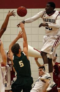 Harvard forward Kyle Casey skies to reject the shot of Dartmouth's Gediminas Bertasius.