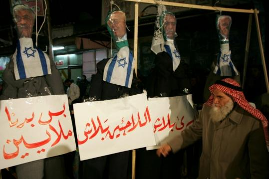 A Hamas supporter stood near effigies of Palestinian Authority leaders decorated with Israeli flags during a rally yesterday in Gaza called by the Islamic militant group.