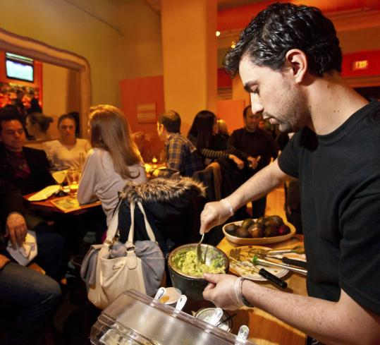 Raphael Vaz (right) makes and serves guacamole at Papagayo in Boston.