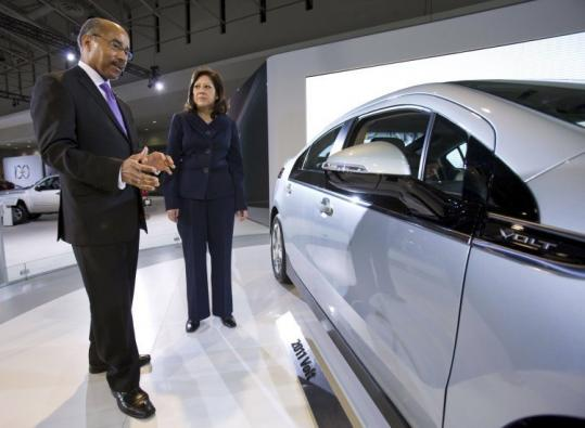 General Motors vice president Ed Welburn shows Hilda Solis, Labor secretary, the Chevrolet Volt in Washington yesterday.