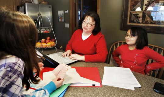 Lisa Chau discussed Girl Scout cookie orders with daughter Willow (right) and friend Abby Flaherty.