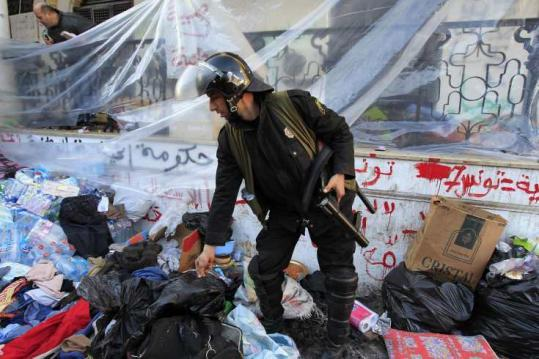 A Tunisian riot police officer searched through belongings of protesters after security forces stormed a protest camp outside the prime minister's office in Tunis yesterday.