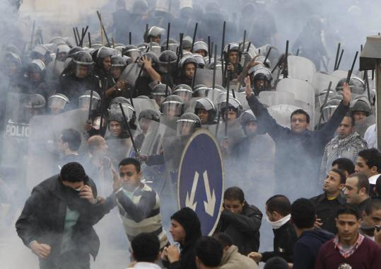 Egyptian protesters clashed with riot police in Cairo yesterday, and activists continued to defy a curfew early today.