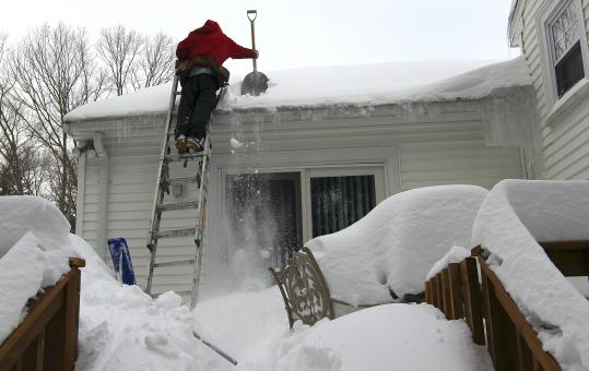 Lois Diaz removed snow from a residence on Deerfield Road in Needham yesterday. Authorities are calling attention to the threat of accumulated snow on roofs.