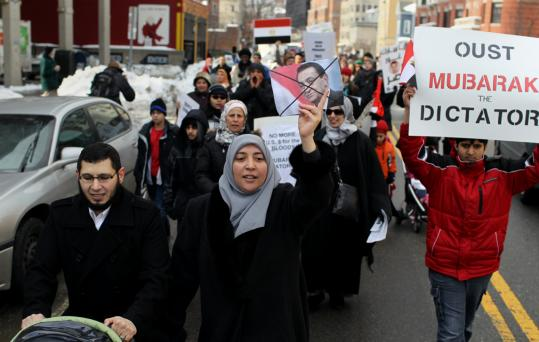 Ahmed Rashed (left) and his wife, Shaimaa Badr, were among hundreds who marched down Massachusetts Avenue in Cambridge to protest the regime of President Hosni Mubarak.