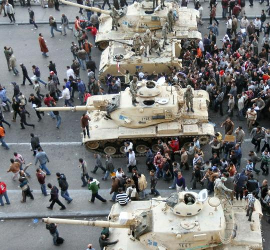 Demonstrators demanding the ouster of President Hosni Mubarak filed passed Egyptian Army tanks in Cairo yesterday.