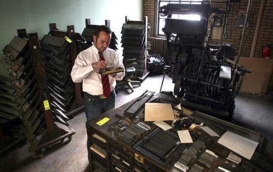 Auctioneer MatthewPaine looked at old lead letters near a linotype press at the defunct printing plant in the North End. The items will be auctioned.