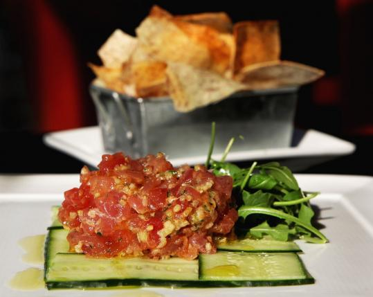 Tuna tartare is prepared tableside, the raw tuna mixed with Sriracha, onion, soy, and ginger and then served over greens.
