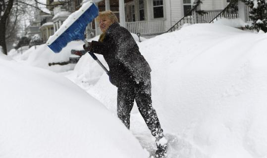 "Diane Dalpe, shoveling snow in front of her home-based photography studio in Arlington, has booked two vacations in sunnier climes, saying, ""I want to wake up and it to be spring out.''"