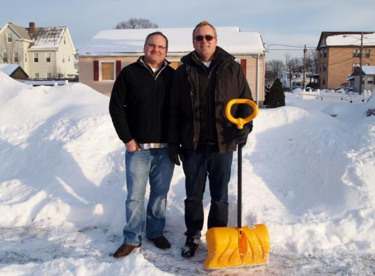 Michael Burns (left) and Bob Houser, at the site of their destroyed home in Hyde Park's Readville section, have endured endless red tape and challenges since the natural gas explosion.
