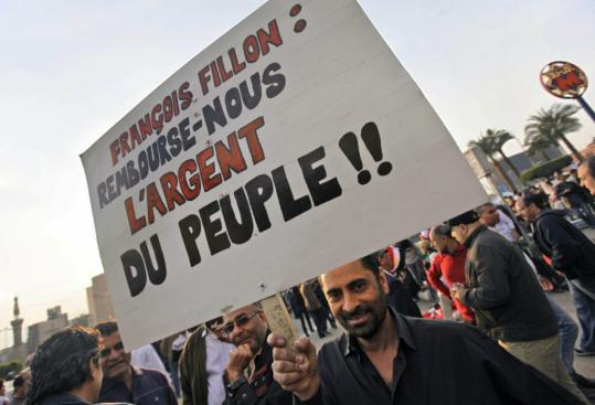 "An Egyptian antigovernment demonstrator's sign in French alluded to a junket to Egypt by France's prime minster, Francois Fillon, saying, ""Pay us back the money of the people!''"