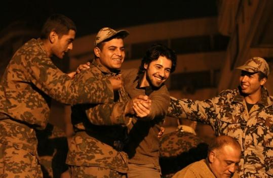 An Egyptian antigovernment protester danced with a soldier during celebrations at Tahrir Square in Cairo.