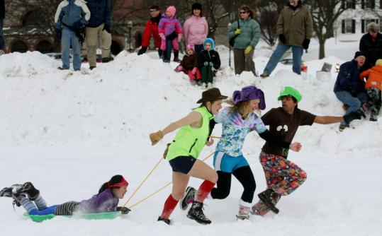 Dartmouth students, left to right, Renee Lai (on sled), Jocelyn Powelson, Kristen Flint, and Solomon Rajput took part in the human dog sled race.
