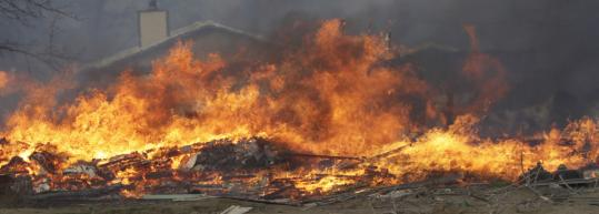 A fire fueled by dry grass and high winds raged through White Swan, Wash., on Saturday, destroying homes.