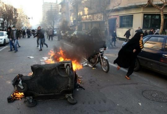 Trash bins were set on fire during yesterday's rally in Tehran. Dozens were arrested for participating in the banned protest.