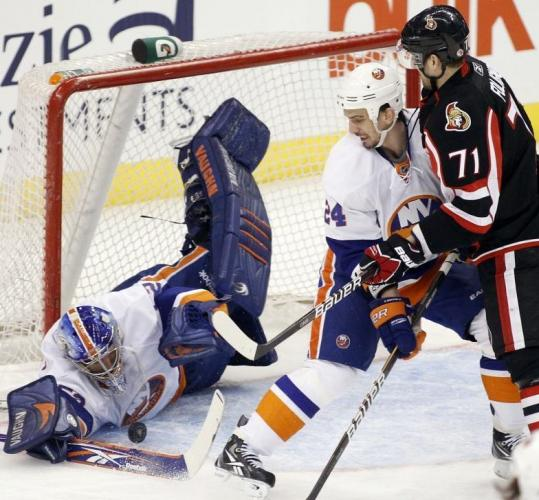Islanders goalie Nathan Lowson takes a dive in teaming with Radek Martinek to stop a shot by Ottawa's Nick Foligno.