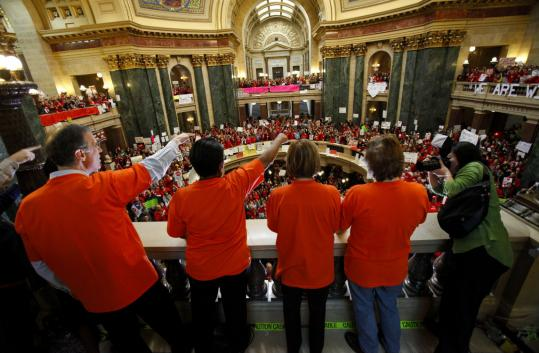 Democrats in Wisconsin's Assembly cheered yesterday during protests. Governor Scott Walker's plan would limit collective bargaining for most government employees to only include wages.