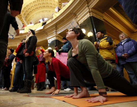 Alicia Wright (right) and Andrea Russell practiced yoga in the rotunda of the Capitol in Madison, Wis., joining protests.