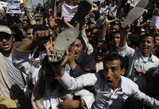 Antigovernment protesters shouted slogans and raised their shoes in Sana, Yemen, yesterday. It was the 10th day of protests.