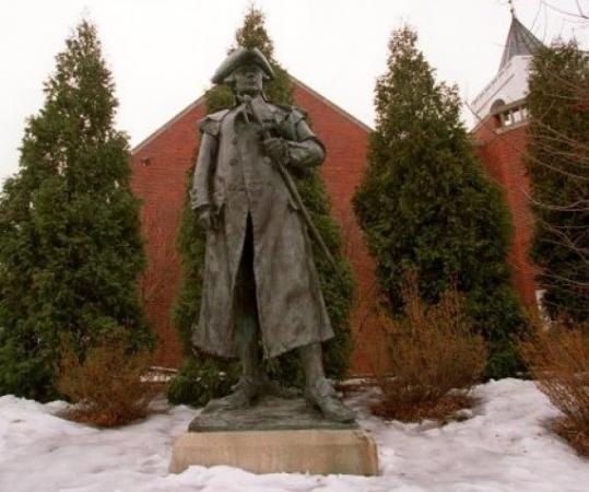 This statue of Joseph Warren has stood inside the courtyard entrance of Roxbury Latin School in West Roxbury since 1969. Some Roxbury residents want it returned to Warren Street.