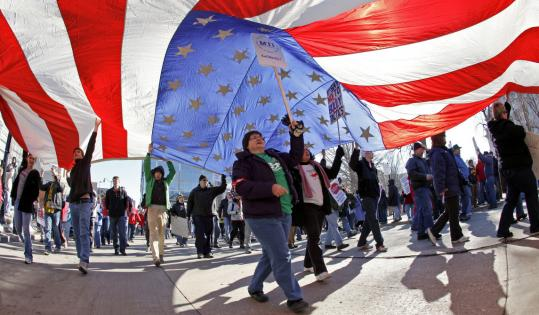 Union members held an American Flag as they marched yesterday in Madison, Wis.