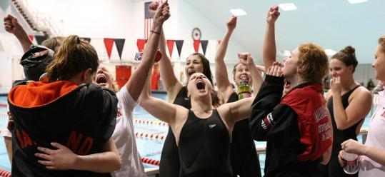Members of the Marblehead girls' swimming team celebrate their Division 2 championship, dethroning five-time defending champion Wayland.