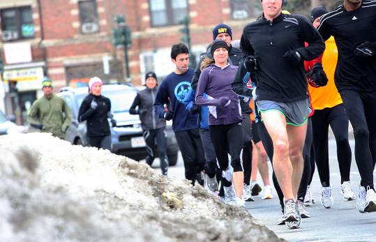 Runners brave the snowbanks and traffic of Commonwealth Avenue in Newton because a path leading from the street to the adjacent carriage road was iced over.