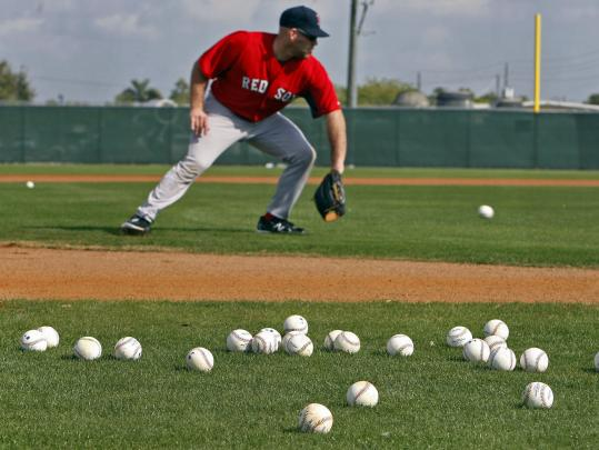 Back at third this season, Kevin Youkilis's fielding was just fine yesterday; in this drill players toss balls they catch off to the side and pick them up later.