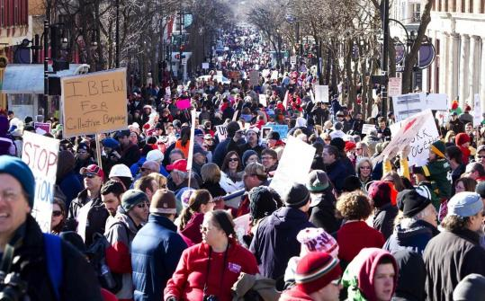 Protesters and pro-labor demonstrators gather down State Street in Madison, Wis. after a rally outside the Wisconsin State Capitol.