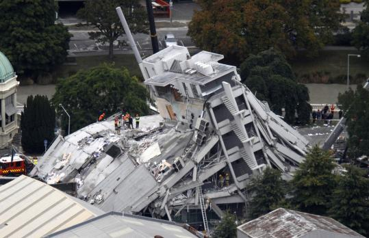 Rescue workers on the collapsed Pyne Gould Guinness Building in central Christchurch. At least 75 people died and 300 hundred are missing after yesterday's earthquake.