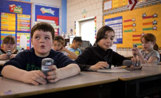 Eight-year-olds Ryan McCarthy, Naomi Diaz, and Isabella Rozzi use electronic response pads in a third grade class at Haverhill's Silver Hill Horace Mann Charter School.