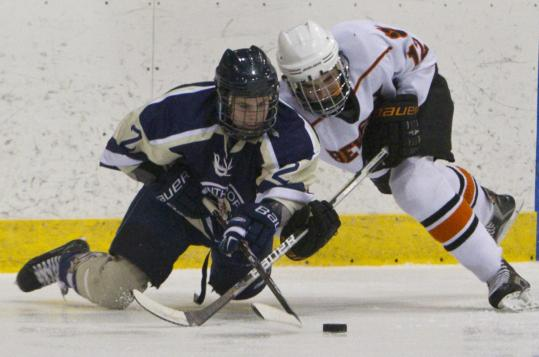 Winthrop High's Chris Page battles with Beverly High's Jack Morency for control of the puck last Saturday.
