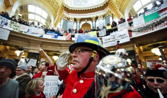 A firefighter saluted as he entered the rotunda of the state Capitol in Madison, Wis., yesterday, on the ninth day of protests over the governor's proposal to curb state worker unions.