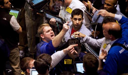 Traders were busy in the crude oil pit at the New York Mercantile Exchange yesterday as oil settled at just under $100 a barrel.