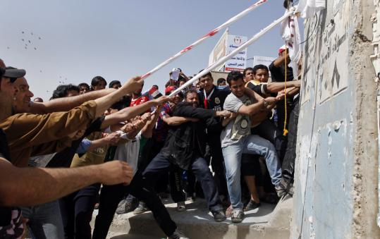 Protesters pulled concrete blast walls leading to the heavily guarded Green Zone during a protest in Baghdad yesterday. Unlike protesters in other Arab countries, the Iraqis were not calling for a new government, but for reforms from Iraq's elected leaders.