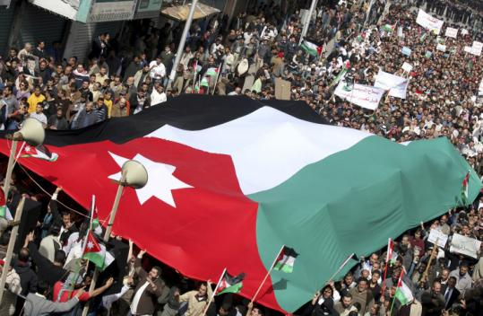 Supporters of the Islamic Action Front carried a giant national flag as they marched in protest yesterday in Amman, Jordan.