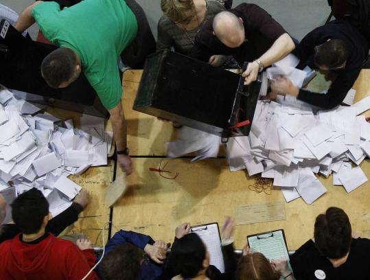 Workers emptied ballot boxes yesterday at the Royal Dublin Society center.
