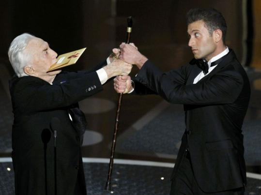 Kirk Douglas tries to wrestle his cane away from an awards escort during the ceremony.