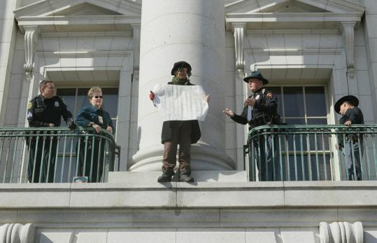 Police tried to get a protester to leave a ledge at the Wisconsin Capitol building yesterday. Demonstrators oppose a bill that would restrict collective bargaining for government workers.