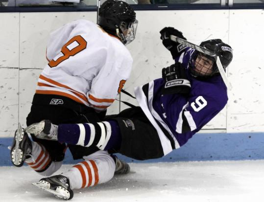 Cathedral's Jordan Kozub tumbles to the ice after colliding with Woburn's Cole Connolly.