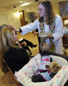 The Rev. Thea Keith-Lucas blesses a pet owner and her dogs at a recent service.