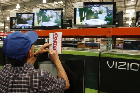 A shopper noted television prices at Costco in Glendale, Calif., on Monday. Retailers reported solid revenue increases for February, extending momentum from a strong holiday season.