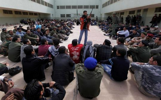 A former Libyan Army soldier showed rebel recruits how to use an AK-47 during training yesterday at a base in Benghazi.