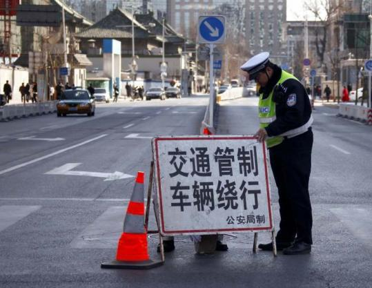 A policeman in Beijing adjusted a sign declaring a road closure near the area of Wangfujing, where reporters were videotaped.