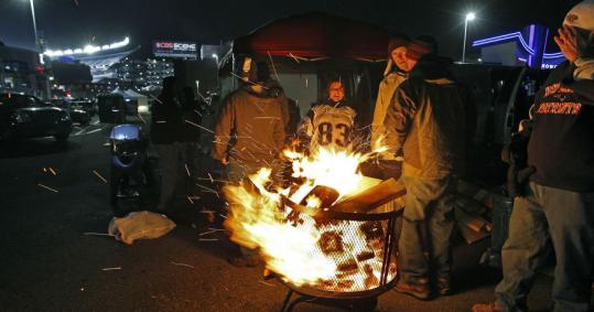 Fans tried to keep warm outside Gillette Stadium prior to the Patriots' game against the New York Jets in December. A record 95 people were taken into protective custody that night, officials say. Another 16 were arrested for crimes.